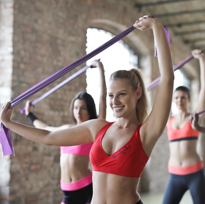 Multiple women in sport clothing exercising with yoga elastics
